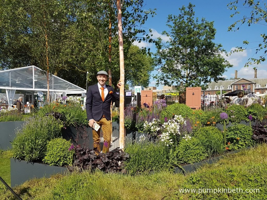 Garden Designer Lee Bestall in The Sir Simon Milton Foundation Urban Connections Garden he designed for the 2016 RHS Chelsea Flower Show. This Fresh Garden was sponsored by Victoria Business Improvement District. This Fresh Garden was designed by Lee Bestall and built by Jon Housley. Isolation and loneliness is a problem for our society, many older people, particularly in urban environments, can feel lonely and isolated, The Urban Connections Garden demonstrates how the power of love and friendship can remove these feelings of melancholy, gloom and loneliness, by bringing people together in high quality communal gardens that bring about a sense of belonging, a feeling of happiness with the opportunity to make new friends and rejoice in the feeling of companionship. Garden designer, Lee Bestall, has carefully chosen the plants for The Sir Simon Milton Foundation Urban Connections Garden, choosing symbiotic plants, that are known to grow better together, to further re-enforces the message of the garden – that people are better together. The silver birch trees that feature in this garden are designed to act like beacons, drawing people in and guiding visitors to the oak seating, where they can relax, enjoy the garden and meet new friends. A new hardy, hybrid orchid – Dactylorhiza 'Simon Milton' is featured in this garden, named after the conservative politician, who died in April 2011, aged 49. Sir Simon Milton's legacy and beliefs of providing training and jobs to young people, and including the older generation within a community that values and appreciates their contribution and encourages their involvement inspires The Sir Simon Milton Foundation and its charitable work.