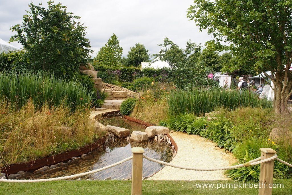 Zoflora: Outstanding Natural Beauty was designed by Helen Elks-Smith, and built by Wycliffe Landscapes Ltd. This Show Garden was sponsored by Zoflora. The RHS judges awarded the garden a Gold Medal and the prestigious title of Best Construction Award, at the RHS Hampton Court Palace Flower Show 2016. The design for this Show Garden was inspired by the patterns and materials found in Yorkshire. The drystone walls define the garden with their curving shape which echoes the curves and stone in the waterways.