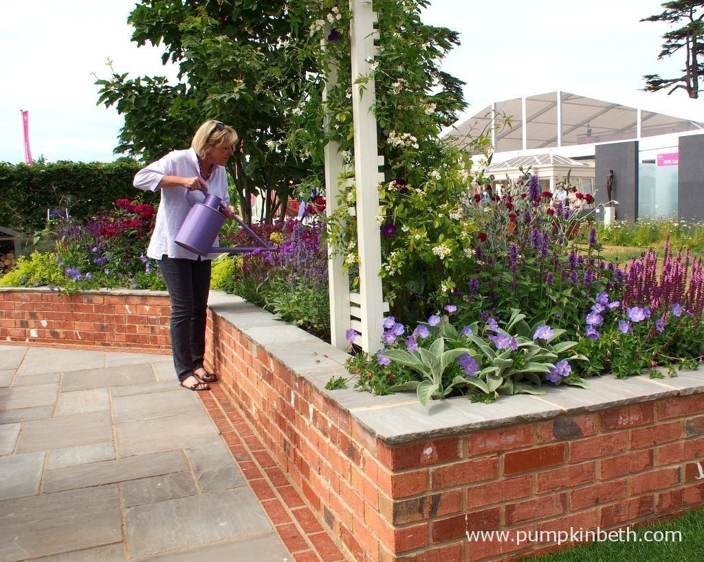 Tracy Foster tending her plants in the garden she designed for the Hampton Court Palace Flower Show Garden, 'A Garden for every Retiree', sponsored by Just Retirement.