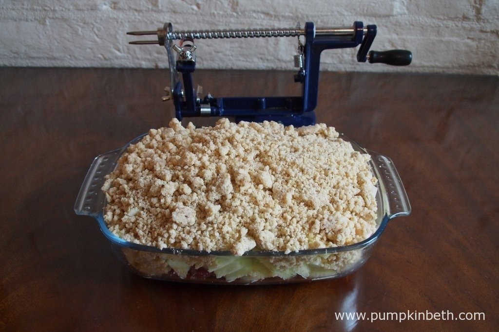 A freshly made apple and raspberry crumble, ready to go in the oven. The apples in this crumble were cored, peeled and sliced using Lakeland's Apple Master, which you can see behind.