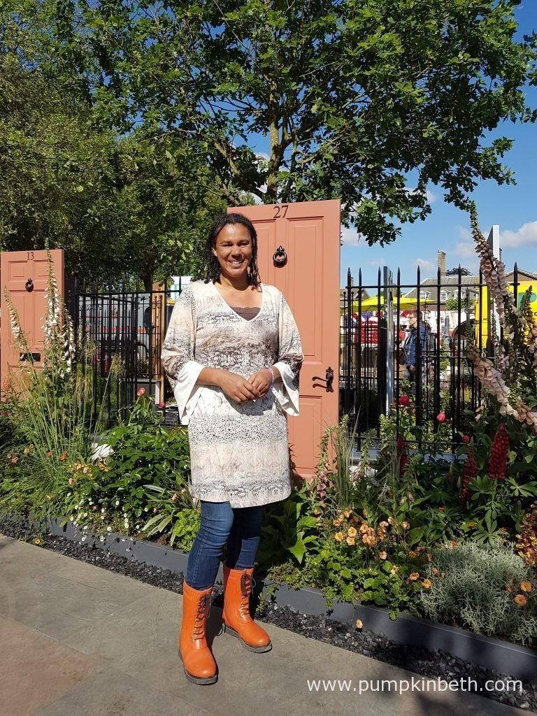 Garden Designer Juliet Sargeant pictured with The Modern Slavery Garden she designed for the RHS Chelsea Flower Show 2016. This Fresh Garden was built by The Outdoor Room and sponsored by The Modern Slavery Campaign. In March 2015, the British Parliament passed the Modern Slavery Act, The Modern Slavery Garden is a celebration of that day. The Modern Slavery Garden is also about looking to the future, when there will be no slaves. The brightly coloured front doors featured in this garden, symbolise the everyday houses and streets that we live on, in contrast, the centre of the garden conflicts with the cheerfully coloured doors, its darker centre depicts the harsh reality - that in the UK there are people held captive and forced to work against their will. The Modern Slavery Garden is designed to raise awareness of the plight of the 13,000 people, who today live and work as slaves in the UK, and the 27 million slaves held worldwide. William Wilberforce stood under an English oak tree in Sussex, when he pledged to dedicate his life to ending slavery in the 1800s. This oak tree lives on today. As a reference to Wilberforce's pledge and to signify hope, steadfastness and dependability, an oak tree stands, as a prominent feature within the garden. A path designed to signify release and freedom, follows open doors and leads out of the garden.