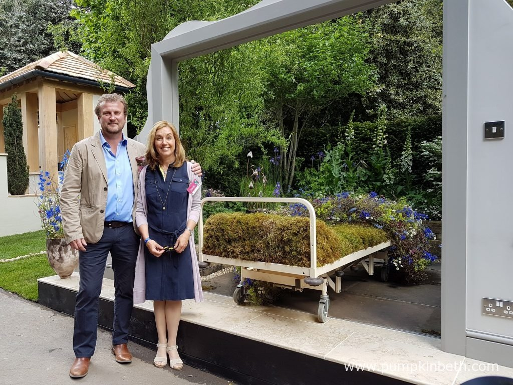 Stephen Welch and Alison Doxey pictured with the Artisan Garden they designed for the RHS Chelsea Flower Show 2016. The Garden Bed a partnership with Asda, was designed by Stephen Welch & Alison Doxey, and built by Frosts Landscapes. To celebrate their 50th birthdays, lifelong friends Alison Doxey and Stephen Welch have joined forces to create this Artisan Garden at the RHS Chelsea Flower Show 2016. Designed to show how easily patients' beds can be moved into the garden, and demonstrate how this simple concept improves the wellbeing of patients and their families. Stephen and Alison took their inspiration from a garden Stephen designed at Les Bourgs Hospice in Guernsey, providing a view of the garden from a patient's bed, to show the patient's perspective. Within the garden, Alison, an accomplished florist, has constructed a quilt made from naturally gathered materials for the symbolic patient's bed. Using 15 meters of plant material, Alison has crafted the most beautiful quilt, by weaving and intwining the natural materials to create a quilt to cover the hospice bed inside the garden.
